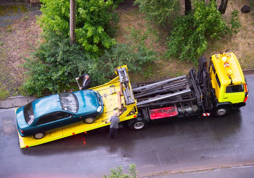 Loading broken car on a tow truck on a road. Aerial view